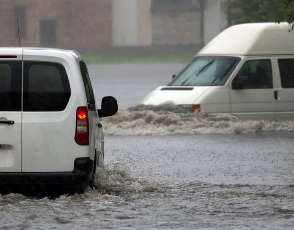 Two vans driving in flood waters
