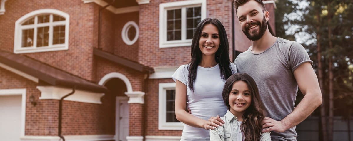 Family standing in front of a home