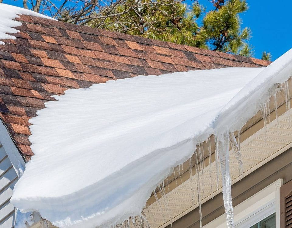 Roof with damaged shingles covered in snow