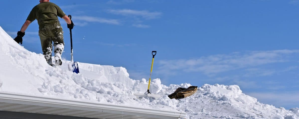 Snow is being removed from a roof with a shovel after a heavy snowfall