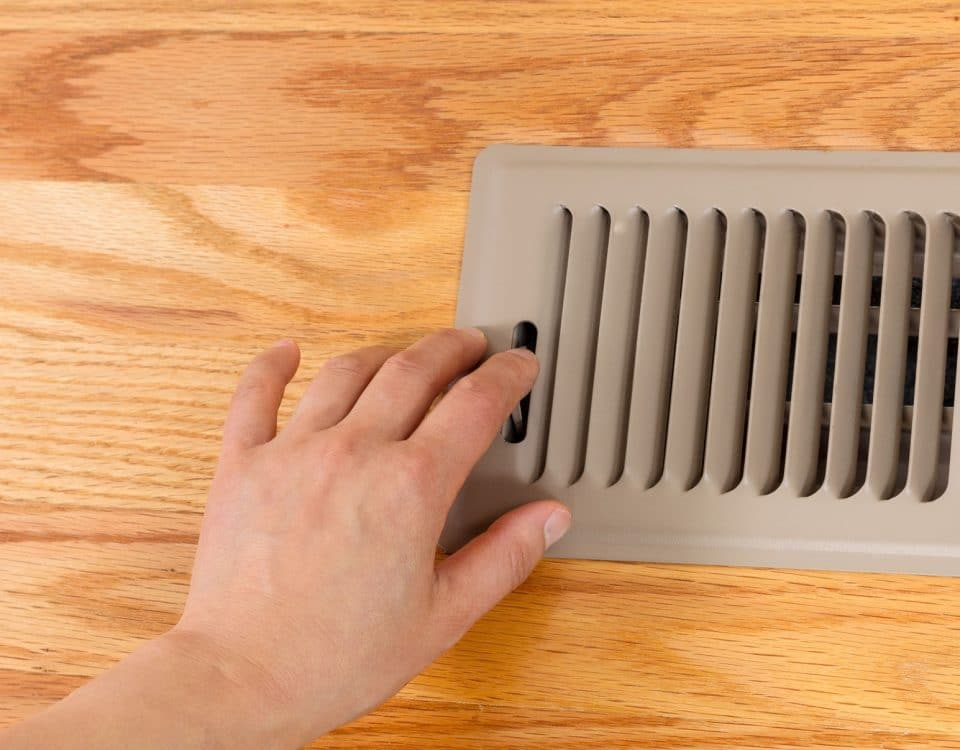Female hand opening up heater floor vent with Red Oak Floors
